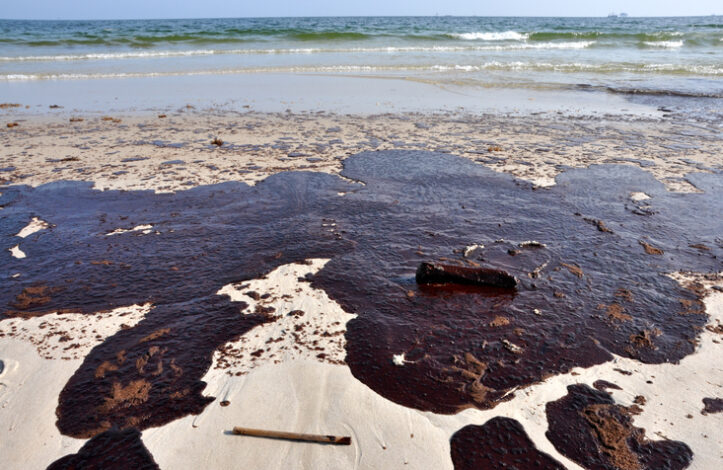 Oil spill on beach with off shore oil rig in background.